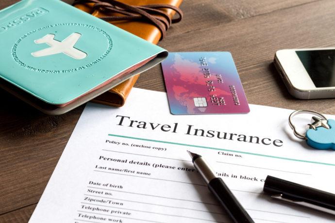travel insurance, credit card, pen, passport leather journal, desk