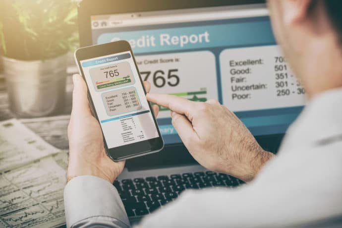 Man checking credit score on computer and cell phone