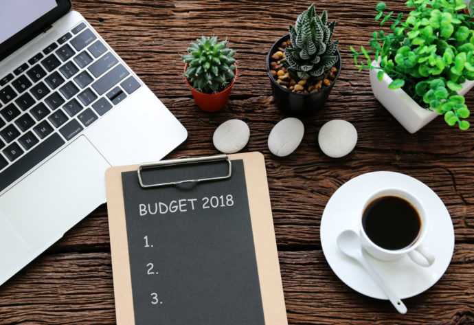 laptop, keyboard with 2018 budget goals, plants, cup of coffee