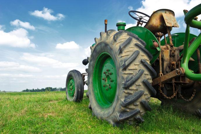 Green tractor on open grassy field, farm equipment loans